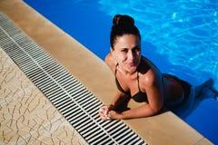 微笑的女孩,当倾斜在水池边缘时 免版税库存图片