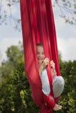 微笑的女孩,当垂悬从织品时 免版税库存照片