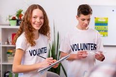 微笑的女孩,当排序与她的最好的朋友的废物在学校时 免版税图库摄影