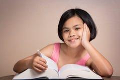 微笑的女孩读书 图库摄影