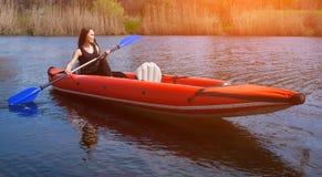 微笑的女孩-有长,黑发的在黑色,运动服女运动员荡桨与在湖的一支桨一个红色,可膨胀的独木舟的 免版税图库摄影