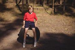 微笑的女孩画象坐巨大的轮胎在障碍桩期间 库存照片