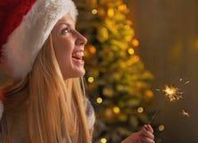 微笑的女孩画象拿着闪烁发光物的圣诞老人帽子的 免版税库存图片