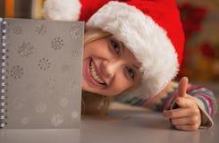 微笑的女孩画象看从日志的圣诞老人帽子的 免版税库存图片