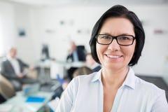 微笑的女实业家佩带的镜片在办公室 免版税库存照片