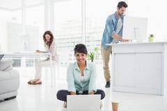 微笑的女实业家坐地板使用膝上型计算机 免版税库存照片