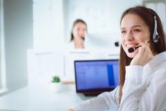 微笑的女实业家或热线服务电话操作员有耳机和计算机的在办公室 免版税库存照片