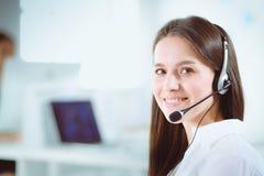 微笑的女实业家或热线服务电话操作员有耳机和计算机的在办公室 图库摄影