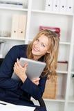 微笑的女实业家拥抱膝上型计算机在办公室 免版税库存照片