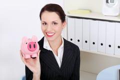 微笑的女实业家挽救金钱在贪心银行中 库存照片