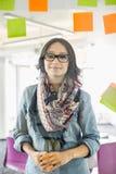 微笑的女实业家支持的玻璃墙画象有稠粘的笔记的在办公室 免版税库存照片