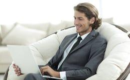 微笑的女实业家特写镜头与膝上型计算机一起使用在客厅 免版税库存照片