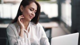 微笑的女实业家画象在咖啡馆,在膝上型计算机的工作,慢动作坐 影视素材