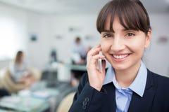微笑的女实业家画象谈话在智能手机在Offic 库存照片
