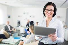 微笑的女实业家藏品数字片剂在办公室 图库摄影