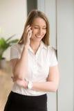 年轻微笑的女实业家谈话在电话,流动communicati 库存图片