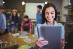 微笑的女实业家,当使用数字式片剂时 库存图片