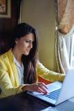 微笑的女实业家,当使用膝上型计算机时 免版税库存图片