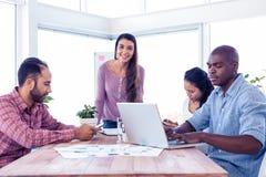 微笑的女实业家画象有工友的在会议室 库存图片