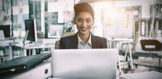 微笑的女实业家画象由书桌的 免版税库存照片