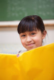 微笑的女小学生读取的纵向 免版税图库摄影