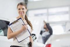 微笑的女性修理工作者画象有剪贴板的在汽车车间 免版税库存照片