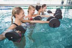微笑的女性健身把做与泡沫哑铃的水色有氧运动分类 免版税库存照片