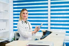 微笑的女性医生佩带洗刷,并且工作在医院招待会,她在片剂写着一个医疗报告 免版税图库摄影