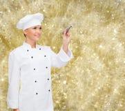 微笑的女性厨师文字某事在空气 免版税库存照片