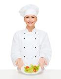 微笑的女性厨师用在板材的沙拉 免版税库存照片