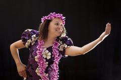 微笑的女性夏威夷女孩跳舞和唱歌与乐器喜欢尤克里里琴 免版税库存图片