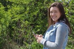 微笑的女性学院/大学生户外,固定的单元电话手机 免版税库存照片