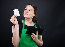 微笑的女性干事藏品参观卡片在手中 免版税图库摄影