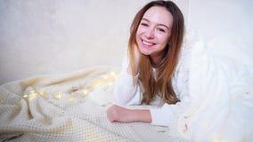 微笑的女性摆在和打手势对照相机,说谎在毯子盖的地板上在明亮的屋子里在诗歌选旁边 股票视频