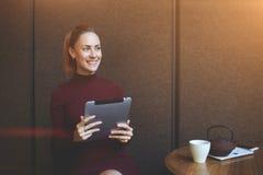 微笑的女性考虑事正面在数字式片剂的工作期间 免版税库存照片