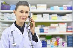 微笑的女性药剂师谈话与某人在药房背景的电话的 免版税图库摄影