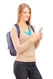 微笑的女性键入在她的移动电话的sms 库存图片