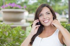 微笑的女性青少年谈话在手机户外在长凳 免版税库存图片