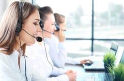 微笑的女性顾客服务代理佩带的耳机画象有工作在背景中的同事的在办公室 免版税库存照片