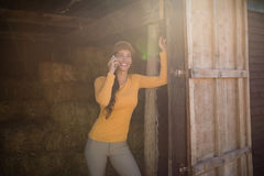 微笑的女性骑师谈话在手机在槽枥 库存照片
