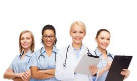 微笑的女性医生和护士有片剂个人计算机的 库存照片