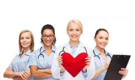 微笑的女性医生和护士有红色心脏的 免版税库存照片