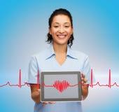 微笑的女性医生或护士有片剂个人计算机的 库存照片