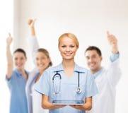 微笑的女性医生或护士有片剂个人计算机的 库存图片