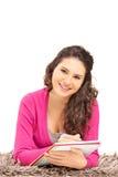微笑的女性说谎在地毯和写在笔记本 库存图片
