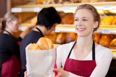 微笑的女推销员在面包店 库存图片