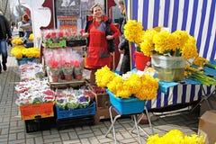 微笑的女推销员在3月8日的国际妇女` s天前卖在市场上的花在伏尔加格勒 库存图片