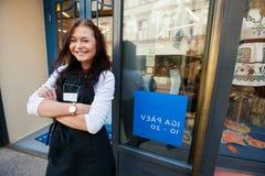 微笑的女推销员常设胳膊画象横渡了外部超级市场 免版税库存照片