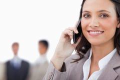 微笑的女推销员联系在电话 免版税库存图片