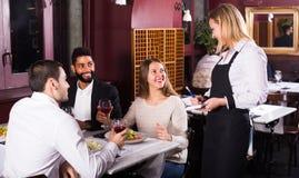 微笑的女服务员和客人在桌上 免版税库存图片